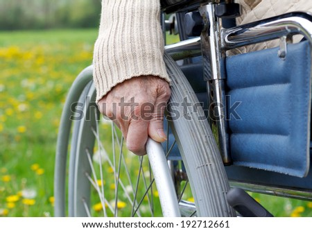Elderly handicapped woman sitting in a wheelchair - stock photo