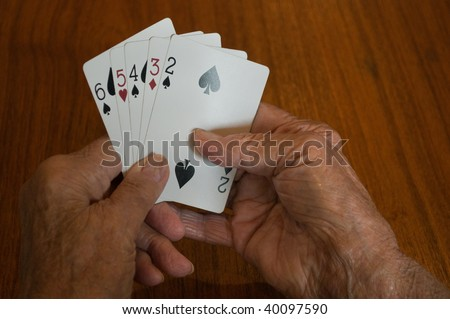 elderly hands holding a bad losing hand of playing cards - stock photo
