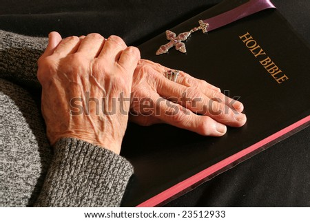 Elderly hands holding the bible - stock photo