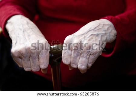elderly hands on cane - stock photo