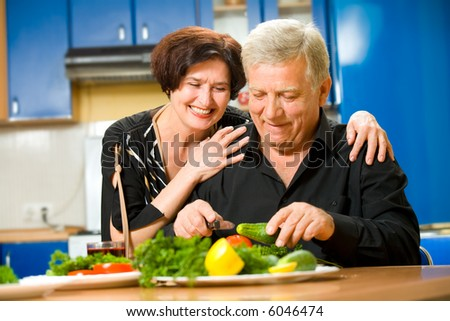 Elderly happy attractive smiling couple cooking at kitchen - stock photo