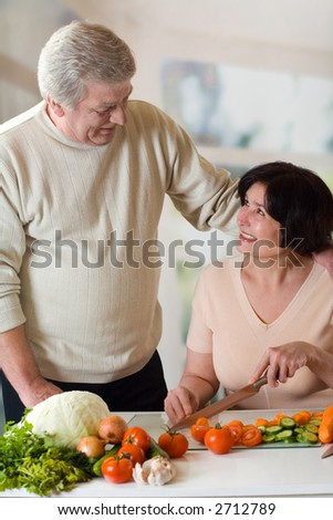 Elderly happy couple cooking at kitchen - stock photo
