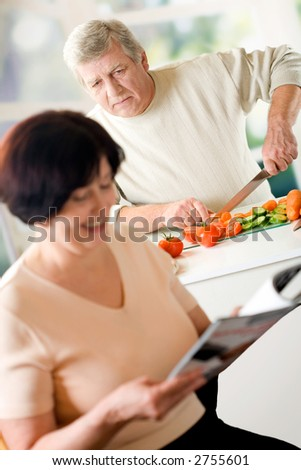 Elderly happy couple cooking at kitchen. Focus on cooking man. - stock photo