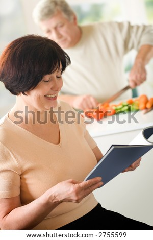 Elderly happy couple cooking at kitchen. Focus on woman. - stock photo
