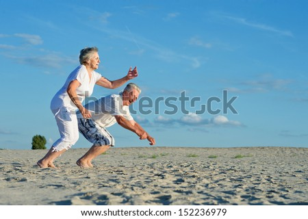 Elderly happy couple having fun in the sand together