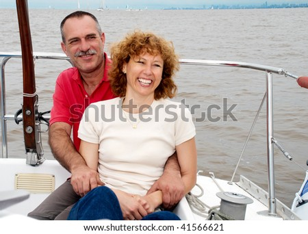 Elderly happy couple onboard the yacht - stock photo