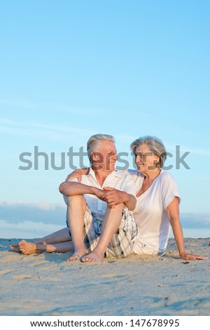Elderly happy couple relaxing in the sand together - stock photo