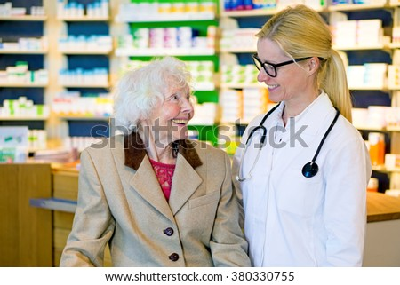 Elderly happy female patient next to smiling doctor with pony tail and eyeglasses standing in front of pharmacy counter - stock photo
