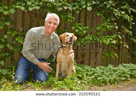 Elderly happy man sitting with labrador retriever in a garden - stock photo