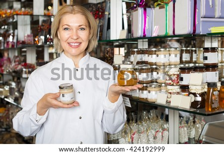 Elderly happy woman selling gifts of fine chocolates and confectionery