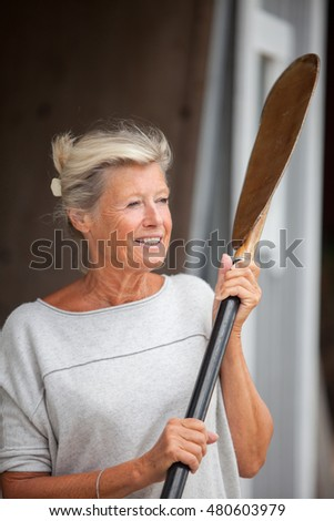 Elderly, healthy looking, Swedish woman with a smile on her lips posing by a boat house with a kayak oar in her hand.