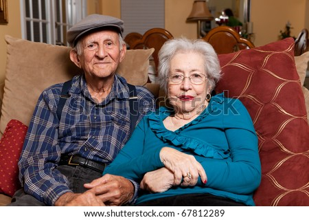 Elderly husband and wife in their 80s in an affectionate pose in a home lifestyle scene. - stock photo
