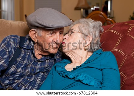 Elderly husband and wife in their 80s in an affectionate pose in a home lifestyle scene.