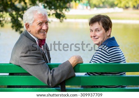 Elderly husband and wife sitting at the lake - stock photo