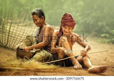 Elderly husband and wife working craft with bamboo. - stock photo