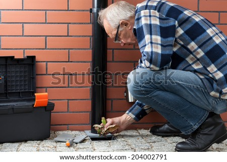 Elderly husband cleaning pavement drain hole from autumn leaves - stock photo
