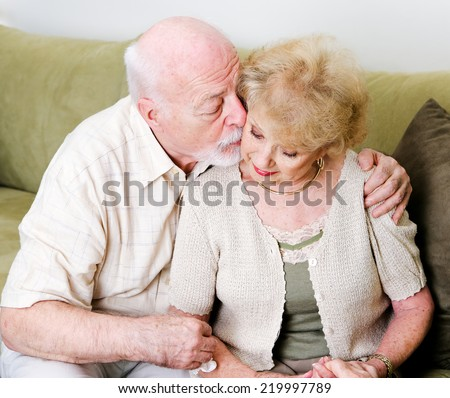 Elderly husband kissing his wife on the cheek in a gesture of consolation and love.