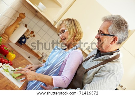Elderly husband watching his wife cutting vegetables in the kitchen - stock photo