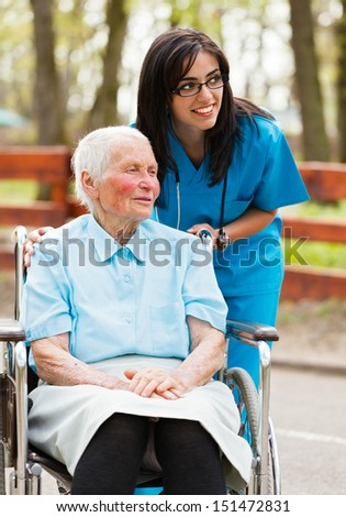 Elderly lady and nurse looking at the arriving visitors.
