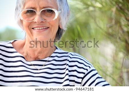 Elderly lady at the beach - stock photo