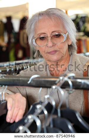 Elderly lady clothes shopping - stock photo