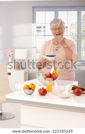 Elderly lady eating blueberry, smiling happy, looking at camera. - stock photo