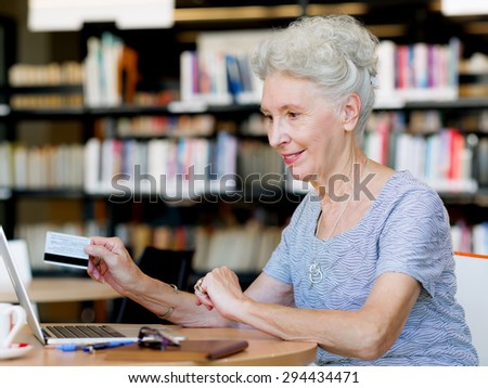 Elderly lady holding a card and working with laptop