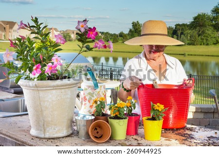 Elderly lady in a wide-brimmed straw sunhat tending to her potted plants on an outdoor patio overlooking a lake as she transplants and waters them in evening light with a delicate sunset - stock photo