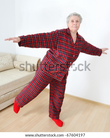elderly lady in pajamas doing gymnastics - stock photo