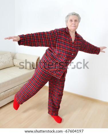 elderly lady in pajamas doing gymnastics - stock photo