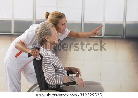 Elderly lady on wheelchair and her nurse - stock photo