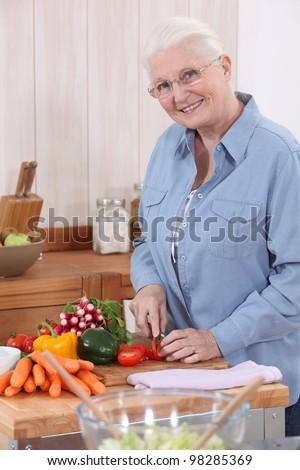 Elderly lady preparing vegetables - stock photo