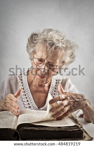 Elderly lady reading an old book
