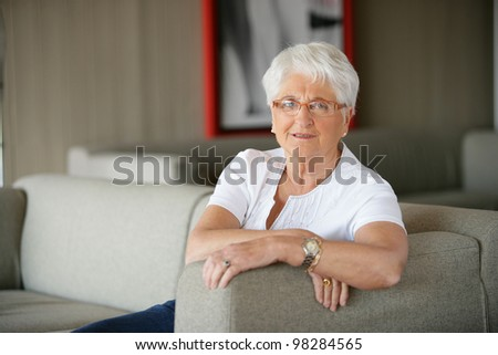 Elderly lady relaxing on sofa
