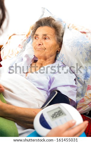 Elderly lady's blood pressure measured by digital gauge. - stock photo
