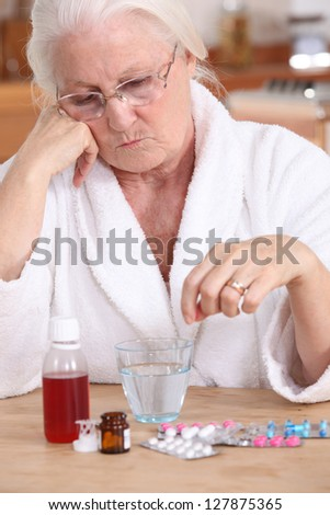 Elderly lady sat with her medication - stock photo
