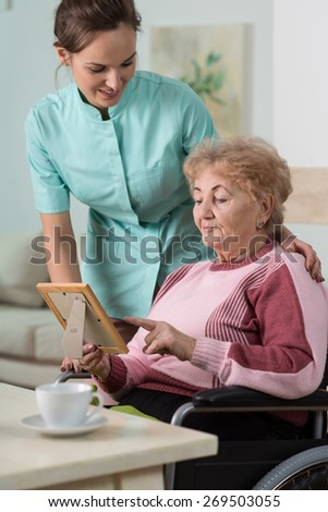 Elderly lady showing a family picture to a nurse