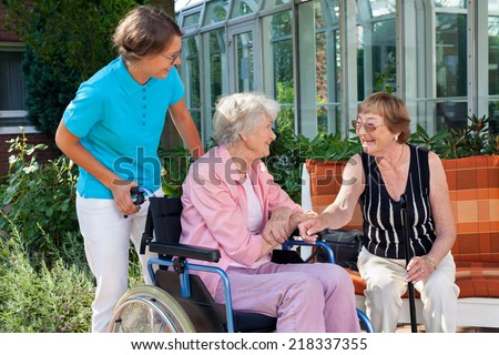 Elderly lady sitting in a wheelchair being pushed by a carer pausing to talk to a friend who is sitting on a wooden garden bench - stock photo