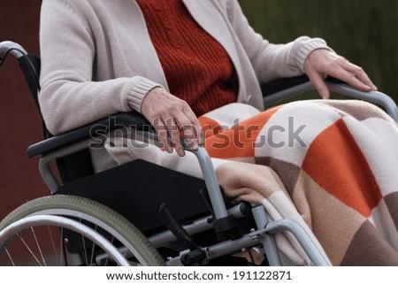 Elderly lady sitting on wheelchair outdoors, horizontal - stock photo