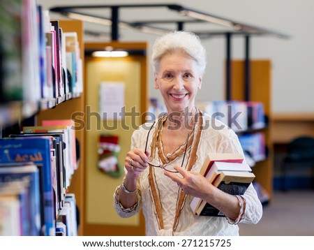 Elderly lady standing next to book shelves in library - stock photo