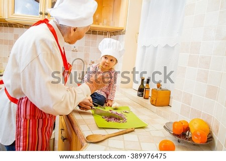 Elderly lady teaching little girl how to cook the best dishes.