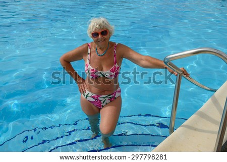 Elderly lady that holds her hand on handrails of swimming pool. - stock photo