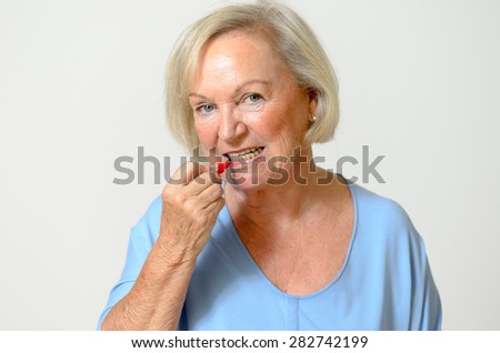 Elderly lady using interdental brush, head and shoulders looking at the camera over a neutral background