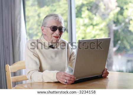 Elderly lady with laptop. Shallow DOF. - stock photo