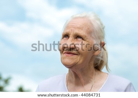 Elderly lovely woman at the blue sky background - stock photo