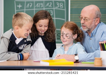 Elderly male teacher sitting at a desk with his young students in class discussing a project - stock photo
