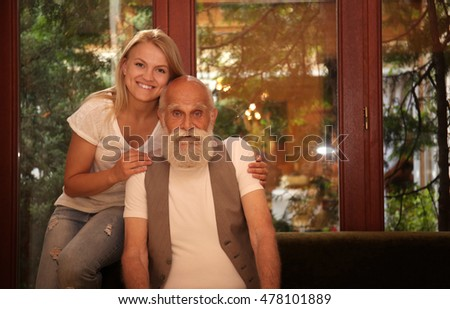 Elderly man and his granddaughter sitting by the window