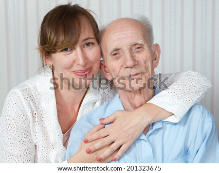 Elderly man and nurse at home. Kind doctor taking care of an old man in wheelchair. Concept of health care for elderly old people, disabled.  - stock photo