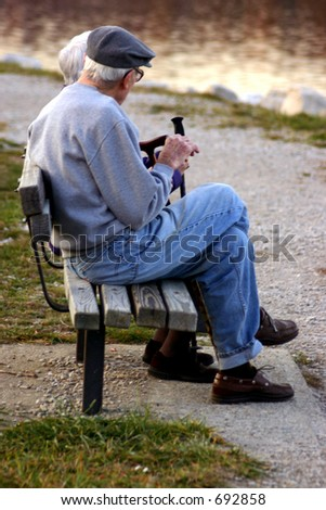 Elderly man and woman sitting on park bench - stock photo