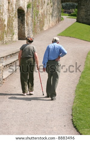 Elderly man and woman walking together along a path with the female holding a walking stick and the man holding his back as if in pain. Rear view. - stock photo